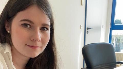 Portrait von Anna Schneiker, wie sie am Schreibtisch sitzt.