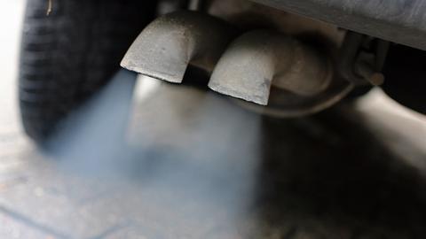 Der Auspuff eines Autos stößt Abgase aus.