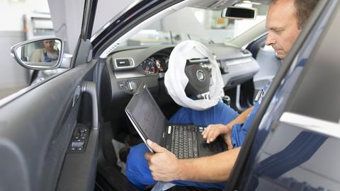 Ein KFZ-Mechatroniker sitzt mit einem Computer im Auto.