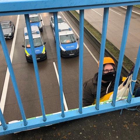 Ein Aktivist seilt sich von der Brücke bei Bersod auf die A5 ab.