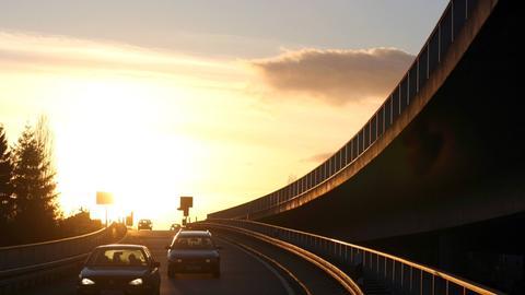 Autos fahren im Sonnenuntergang über die Ausfahrt von einer Hochstraße runter