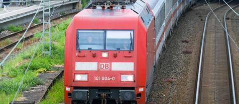 Eine Bahn von vorne, wie sie aus einem Bahnhof fährt. Durch die Windschutzscheibe sind zwei Lokführer zu sehen.