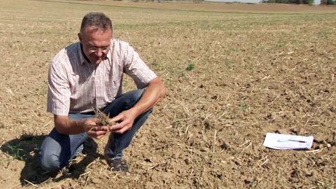 Landwirt Ralf Schaab auf einem Acker in Erbenheim. Er kniet auf dem Boden und hat Erde in seiner Hand.