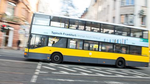 """Ein Bus mit zwei Etagen fährt durch Frankfurt, darauf die Aufschrift: """"Typisch Frankfurt. Immer hoch hinaus."""""""