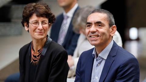 Eine Frau und ein Mann sitzen nebeneinander, beide lächeln.