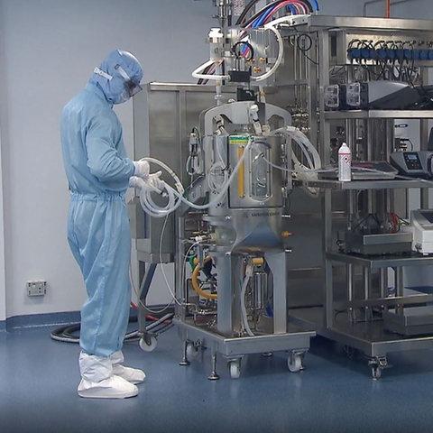 Reinraum im Biontech-Werk in Marburg - drei Menschen in blauen Schutzanzügen bei der Arbeit