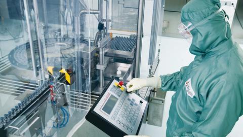 n Angestellter im Schutzanzug arbeitet in der Abfüllstraße der Produktion im Werk der Biotest AG in Dreieich