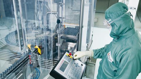 Ein Angestellter im Schutzanzug arbeitet in der Abfüllstraße der Produktion im Werk der Biotest AG in Dreieich