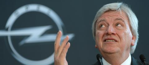 Ministerpräsident Volker Bouffier (CDU) vor einer Wand mit Opel-Logo in Rüsselsheim.