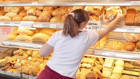 Eine Bäckerin holt ein Brötchen aus dem Regal
