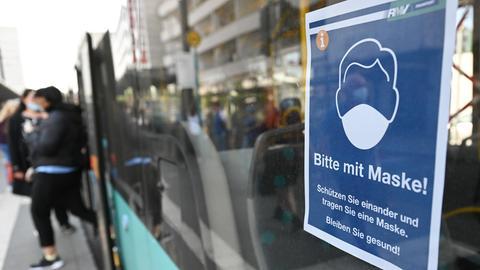 Schild an Bus weist auf Maskenpflicht der Fahrgäste hin