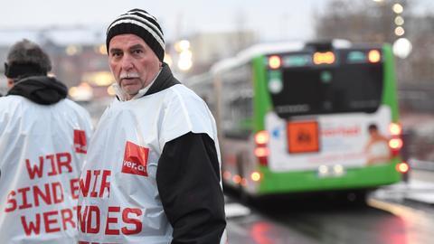 Zwei Menschen mit Streik-Weste vor einem Bus.