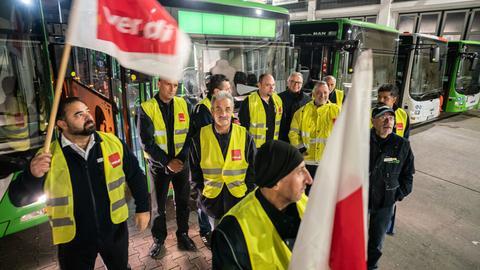 Busfahrer haben sich am frühen morgen beim Streik an ihren im zentralen Offenbacher Busdepot gebliebenen Fahrzeugen aufgestellt.