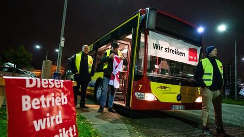 """Busfahrer stehen neben einem Fahrzeug mit einem Banner an der Frontscheibe mit der Aufschrift """"Wir streiken""""."""