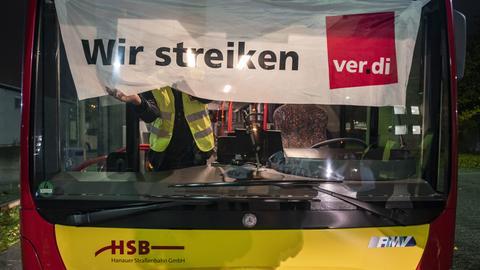 """Ein Busfahrer befestigt in den frühen Morgenstunden ein Banner an der Frontscheibe mit der Aufschrift """"Wir streiken""""."""