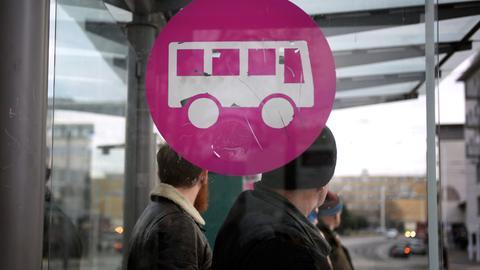 Wartende Menschen an einer Bushaltestelle in Darmstadt