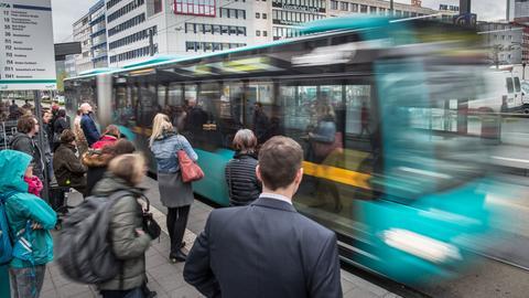Fahrgäste an einer Haltestelle für Busse und Straßenbahnen an der Konstablerwache in Frankfurt.