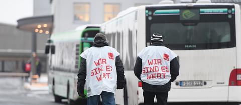 Zwei streikende Busfahrer gehen im Busdepot der RhönEnergie in Fulda an Bussen vorbei