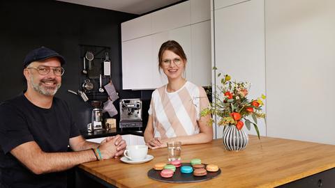 Götz Lindenmayer und Elisabeth Marcard stehen in einer Küche. Im Fokus stehen Kaffeemaschine und passende Utensilien.