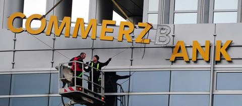 Arbeiter demontieren in Frankfurt den Schriftzug an einer Commerzbankfiliale.