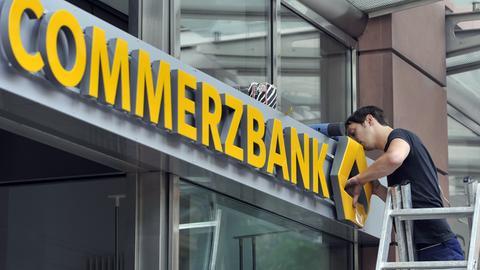 Ein Techniker befestigt das ogo einer Commerzbank-Filiale in Frankfurt
