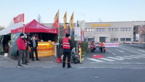 Menschen mit IGM-Fahnen und -Westen stehen und sitzen vor dem Continental-Werk in Karben.
