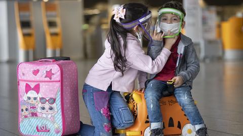 Ein Mädchen und sein Bruder mit Schutzmasken am Flughafen Frankfurt