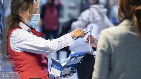Fraport-Mitarbeiterin verteilt Schutzmasken an Passagiere am Flughafen Frankfurt