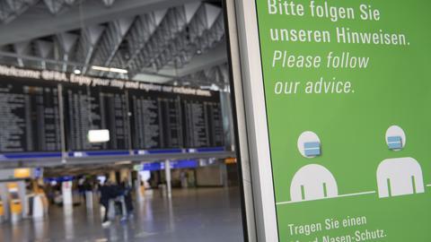 Grünes Plakat mit Hinweis zum Abstandhalten und Masketragen am Flughafen Frankfurt