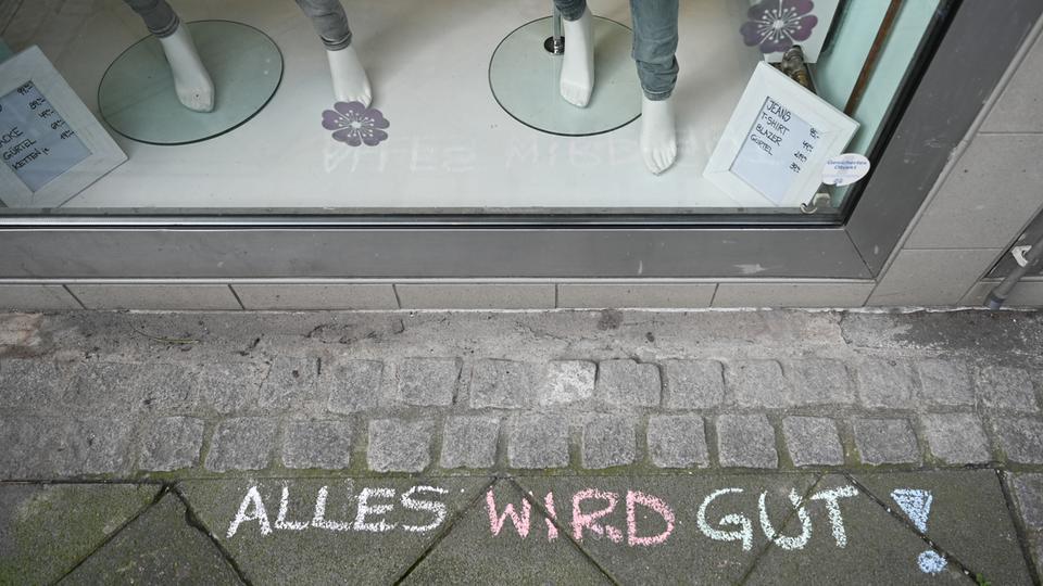 """""""Alles wird gut !"""" ist mit farbiger Kreide vor einer geschlossenen Boutique in Frankfurt auf den Asphalt geschrieben."""