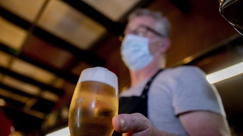 Ein Gastronom mit Mundschutz und Bierglas in der Hand