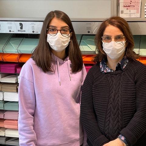 Sarah und Leila Hossini stehen vor einer Wand mit Briefumschlägen und Pappen.