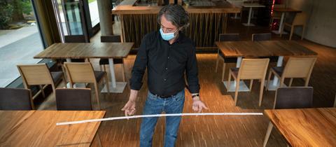 Mensch mit Mundschutz in einem Restaurant mit Zollstock zwischen den Tischen.