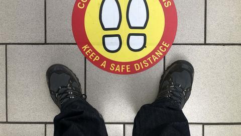 """Arbeiter steht vor einem Schild auf dem Boden mit der Aufschrift """"Keep a safe distance"""""""