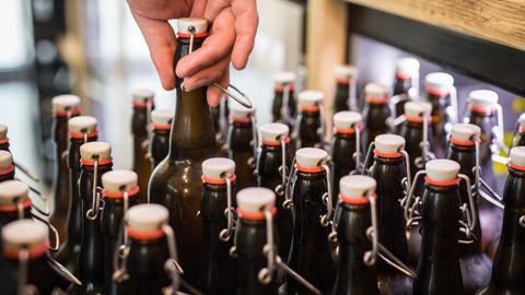 """Ein Kunde nimmt in der kleinen Brauerei """"Braustil"""" eine Flasche aus dem Kühlschrank."""