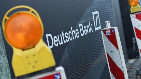 Warnbaken einer Baustelle vor dem Deutsche-Bank-Schriftzug