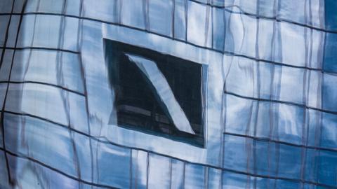 Zentrale und Logo der Deutschen Bank spiegeln sich in einer Glasfassade im Frankfurter Bankenviertel.