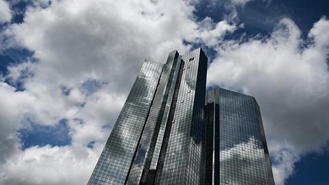 Wolken ziehen über die Zentrale der Deutschen Bank, während sich der Wolkenhimmel in der Fassade spiegelt
