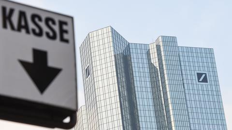 """Ein Schild mit der Aufschrift """"Kasse"""" und einem Pfeil nach unten vor der Deutsche-Bank-Zentrale."""