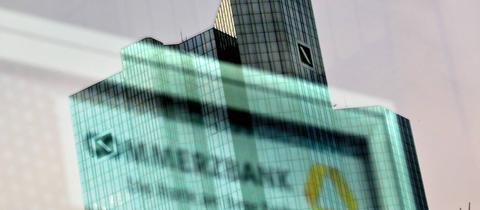 Zwillingstürme der Deutschen Bank gespiegelt in einer Tür einer Commerzbankfiliale
