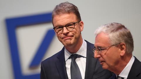 Christian Sewing (l), Vorstandsvorsitzender der Deutschen Bank, und Paul Achleitner, Aufsichtsratsvorsitzender, stehen zu Beginn der Hauptversammlung 2019 der Deutschen Bank in der Frankfurter Festhalle zusammen.