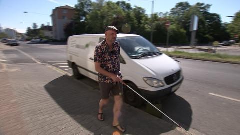 Der Frankfurter Fred Lohr tastet sich mit seinem Blindenstock über einen Gehweg