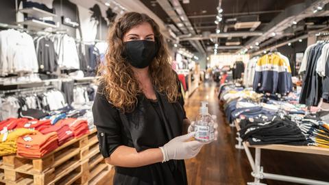 Mit Mundschutz und einem Desinfektionsmittel in der Hand: Eine Laden-Mitarbeiterin im Frankfurter Shoppingcenter MyZeil