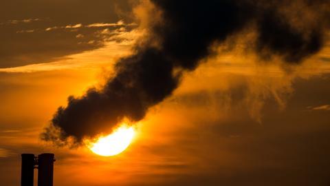 Qualmende Schornsteine eines Blockheizkraftwerkes in der Morgensonne.