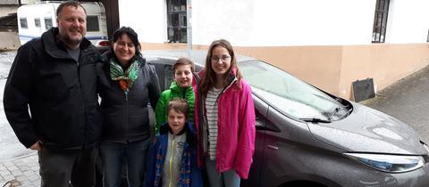 Familie Müller steht vor dem Testfahrzeug