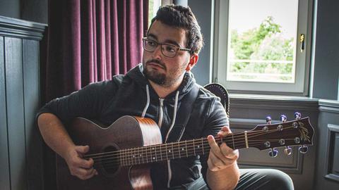 Johannes Napp (ein junger Mann mit Brille und Bart) spielt auf seiner Gitarre.