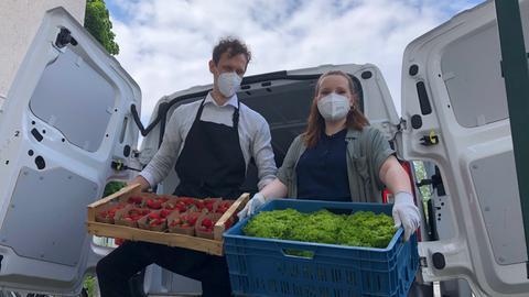 """Simon Block und Melanie Steuer, Inhaber von """"Der Mainbauer"""" - mit Gemüsekisten in den Händen stehen sie vor einem geöffneten Transporter."""