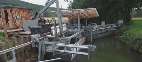 Prototyp der Fangkammer - große metallene Körbe - an einem Fluss