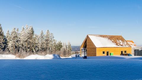 ein Holz-Ferienhaus steht im Schnee am Waldrand