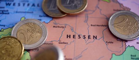 Euro-Münzen liegen auf einer Hessen-Karte.